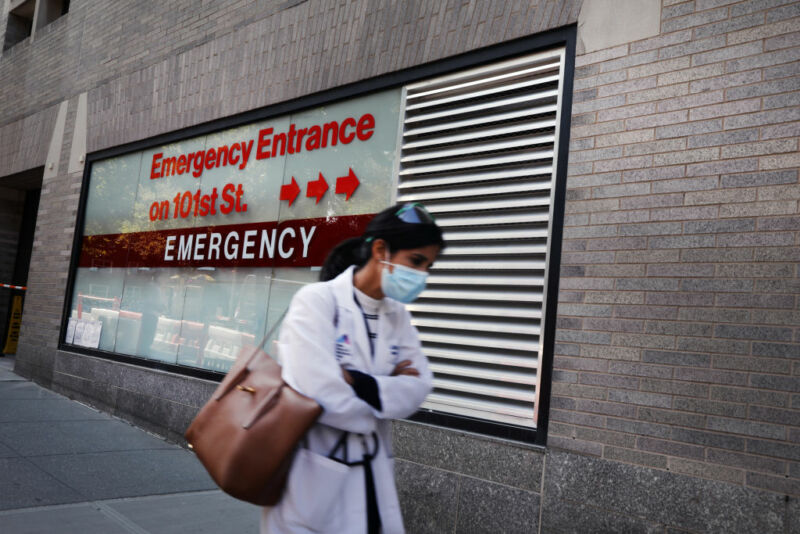 A doctor walks in front of a hospital entrance.