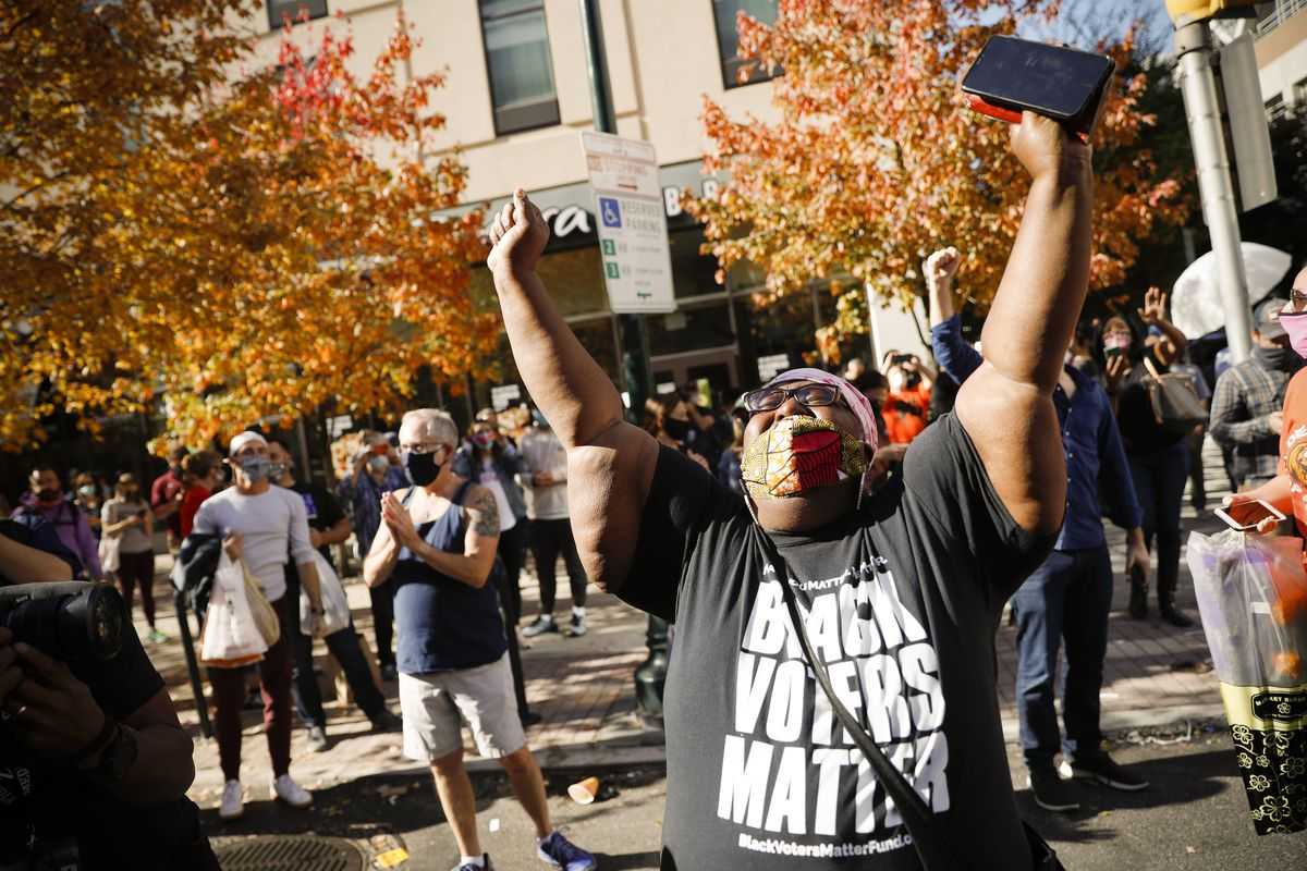 """A Black woman with a kente cloth mask and a black t-shirt that says in bold white letters """"Black Voters Matter"""" raises both her arms in the air. She's framed by trees with gold and red leaves. She seems to be shouting with happiness."""