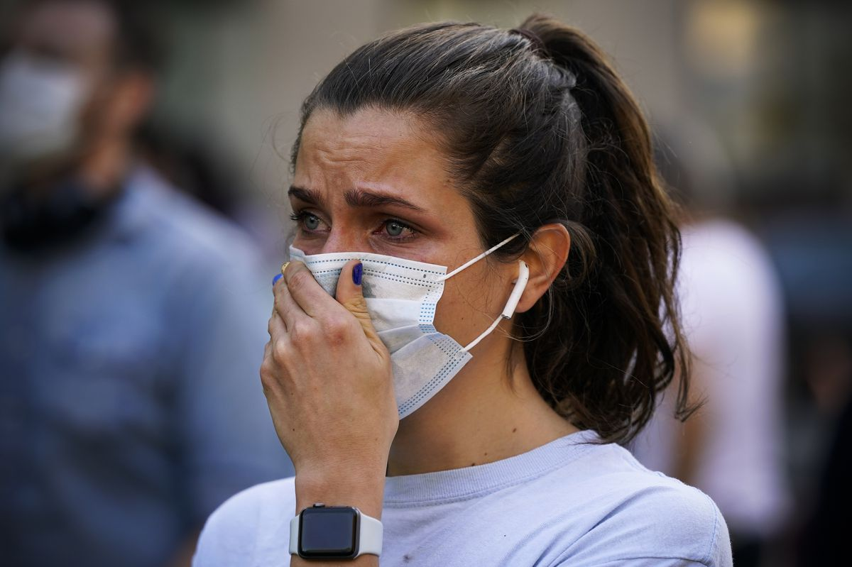 A woman with brown hair puts a hand over her mask. Her eyes are red, as if she has been crying.
