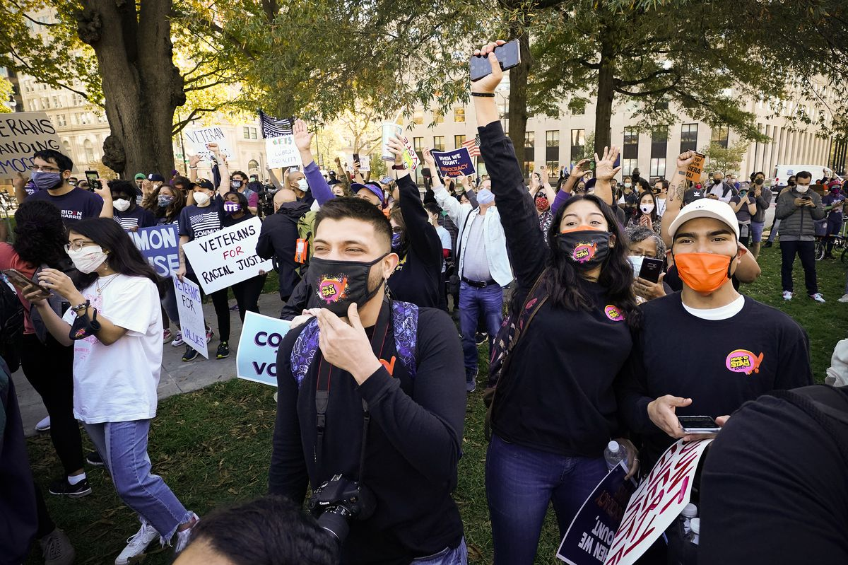 Young adults in black and in orange and black face masks wave, seeming to smile beneath their masks. Behind them is a large crowd, many people's arms in the air.
