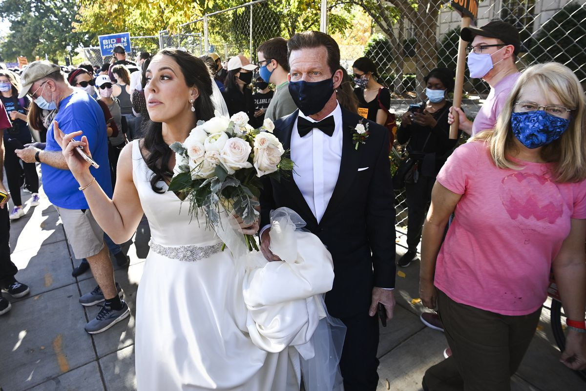 A woman in a white silk bridal gown and holding white flowers walks with a man in a black tuxedo and black mask. They seem overwhelmed as they move through a crowd.