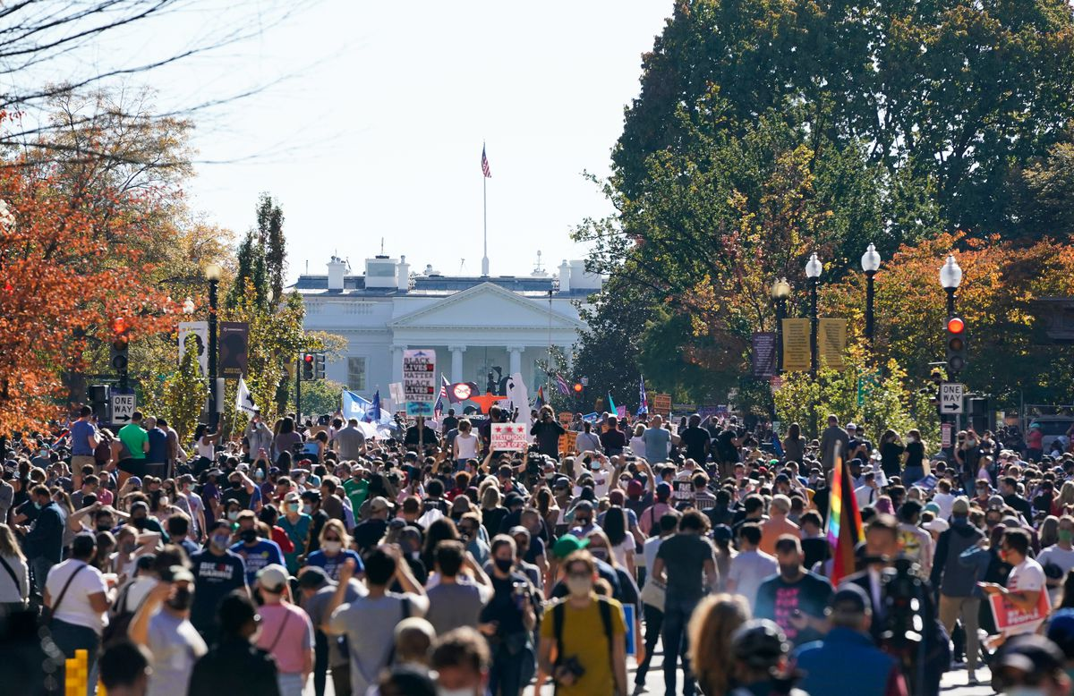 On a road framed by fall trees, the White House stands in the distance. In front of it is a tight mass of people, indistinguishable from one another.