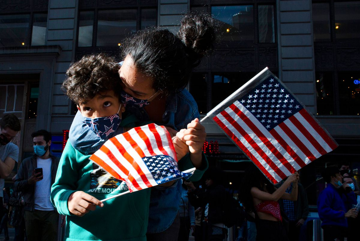 A woman with a stars and stripes mask, and holding a mini US flag, kisses a little boy with curly hair.