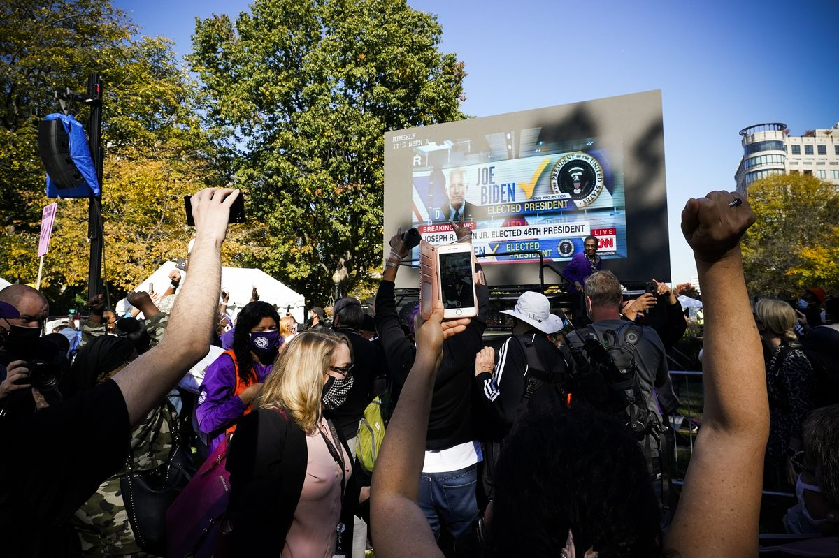 People watch a giant screen set up in a park, and raise their arms in victory as CNN calls the race for Biden.