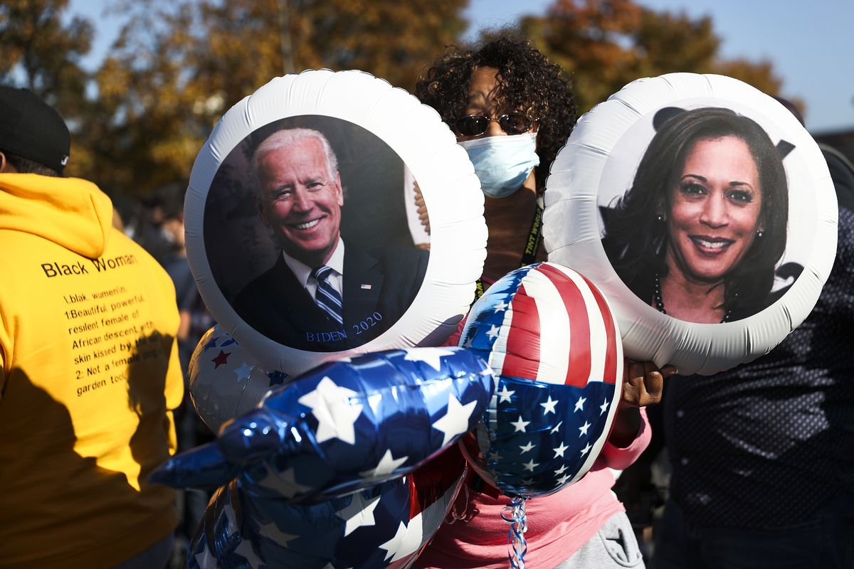 A black woman with a blue mask and curly hair poses with a bevy of balloons — most have US flag patterns, but one has a photo of Harris; the other a photo of Biden.