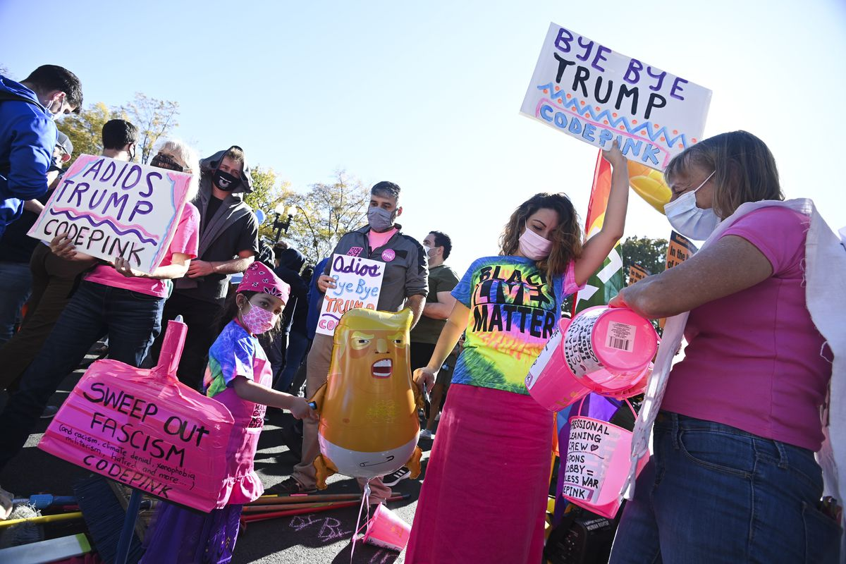 """A group of protesters in pink of all ages — a woman with white hair holds a sign that says """"Adios Trump Code Pink"""" while a little girl holds a balloon of a caricature baby Trump; she also holds a pink oversized dustpan that reads """"Sweep out Fascism."""" Next to the little girl is a young woman with a tie dye Black Lives Matter shirt on; she holds a sign that says """"Bye Bye Trump."""""""