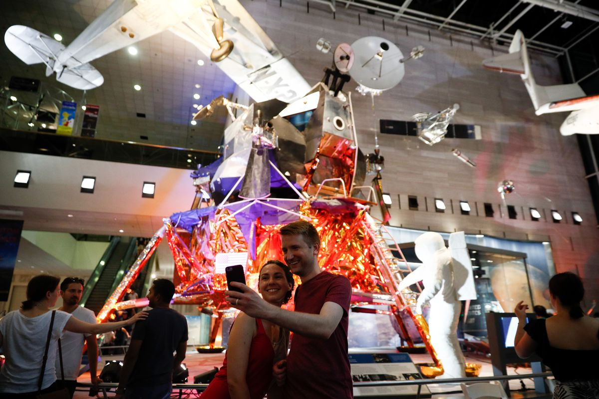 A photo of visitors touring the Smithsonian National Air and Space Museum, with a man and a woman taking a selfie in front of an exhibit.