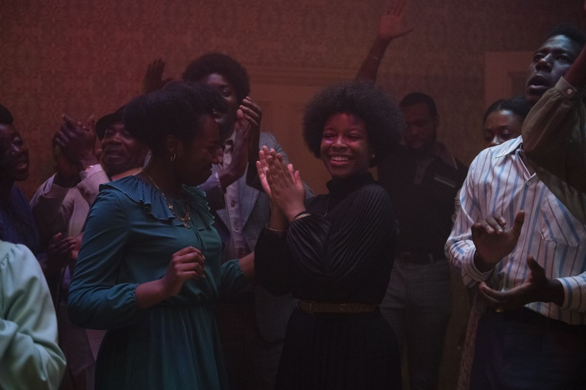 A group of young people dance in a dimly lit room.