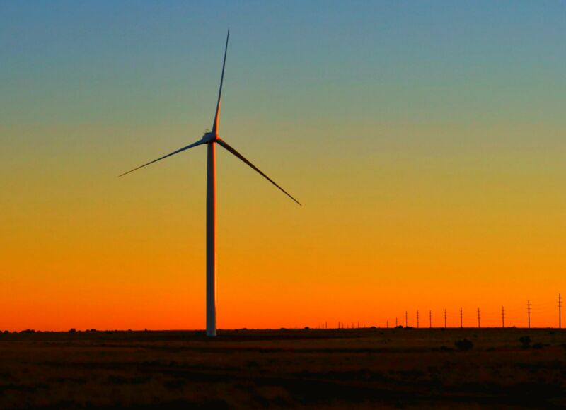 A wind turbine is silhouetted against the sunset.
