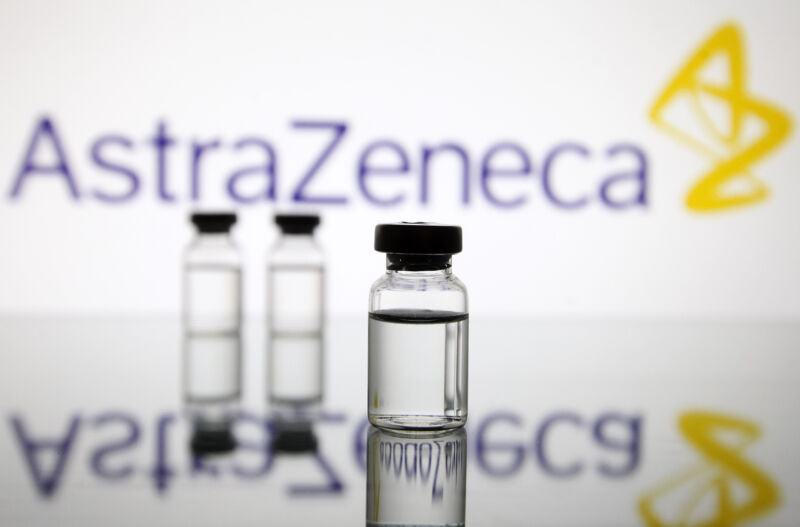 Vials in front of the AstraZeneca British biopharmaceutical company logo are seen in this creative photo taken on 18 November 2020.