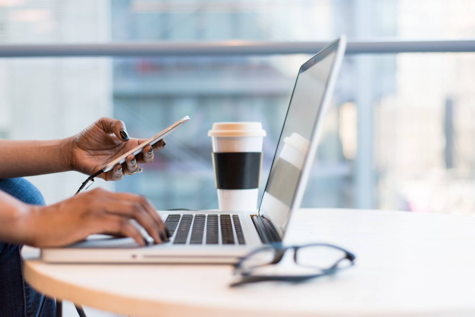 black female remote worker on phone and laptop at desk