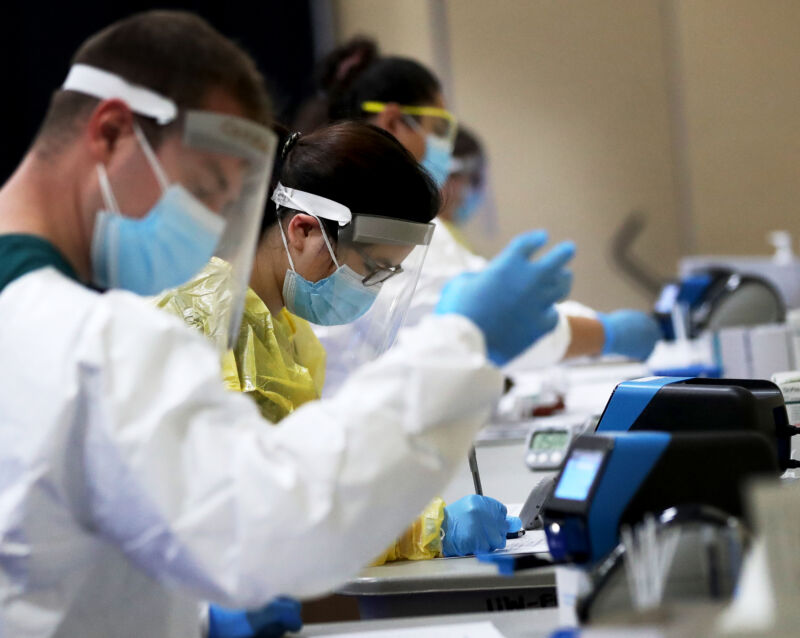 Workers in full gowns, masks, face shields, and gloves work at a table to process tests for COVID-19