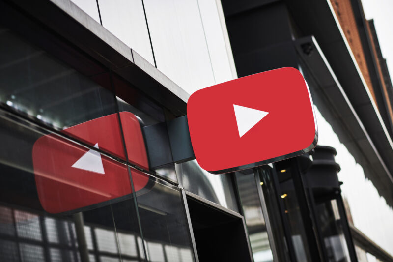 A sign in the shape of the YouTube logo juts out over a glass wall.