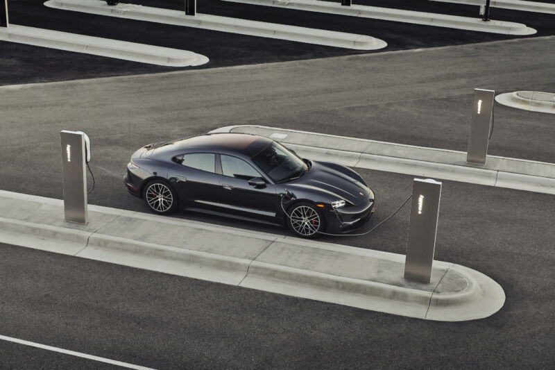 A black Porsche Taycan plugged into a sleek-looking charger
