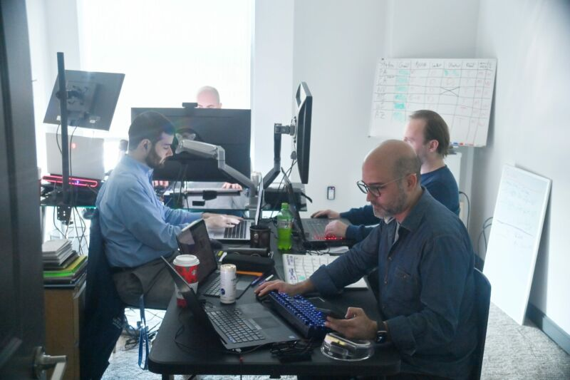 Four men sitting in front of computers in a workplace.