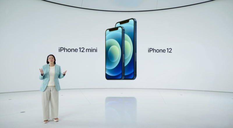 A woman gives a presentation in front of a giant video projector displaying two smartphones.