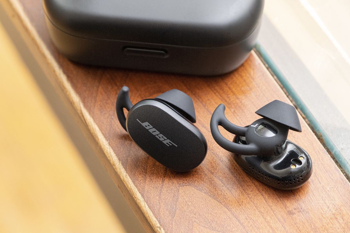 The Bose QuietComfort Earbuds on a table beside the carrying case.