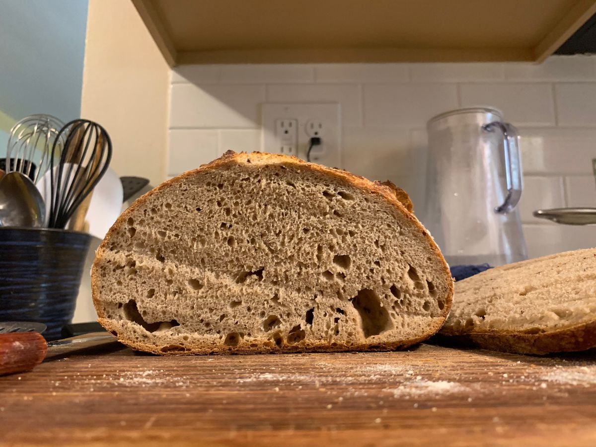 A cross-section of a loaf of bread sitting on a cutting board.