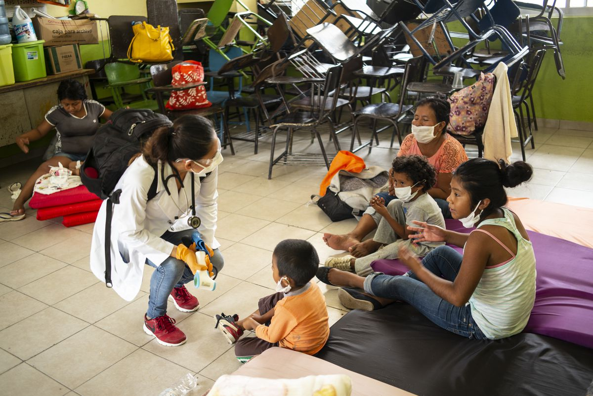 A doctor performs a medical check-up on a family to identify possible cases of COVID-19 at the Heroes del 47 primary school shelter on August 20, 2020 in Cabo San Lucas, Mexico.