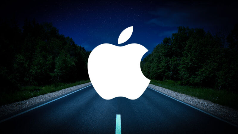 An Apple logo has been photoshopped onto an empty road at night.