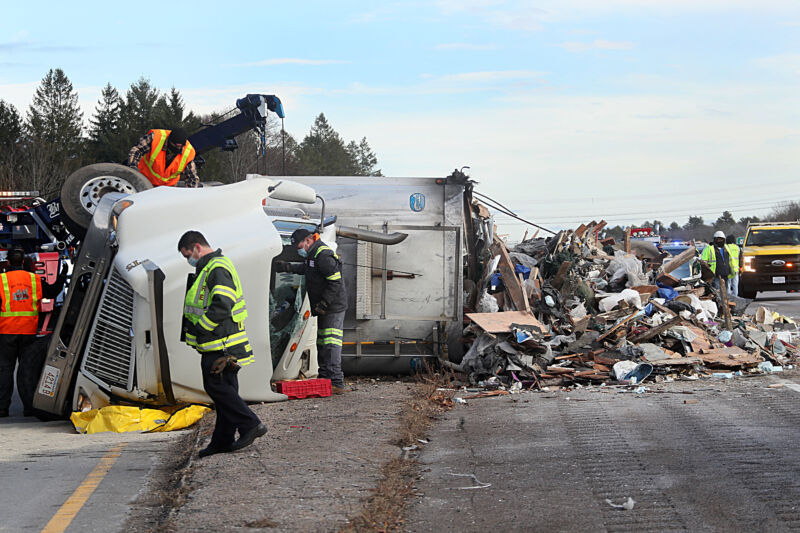 Road workers attend to an overturned semi truck.