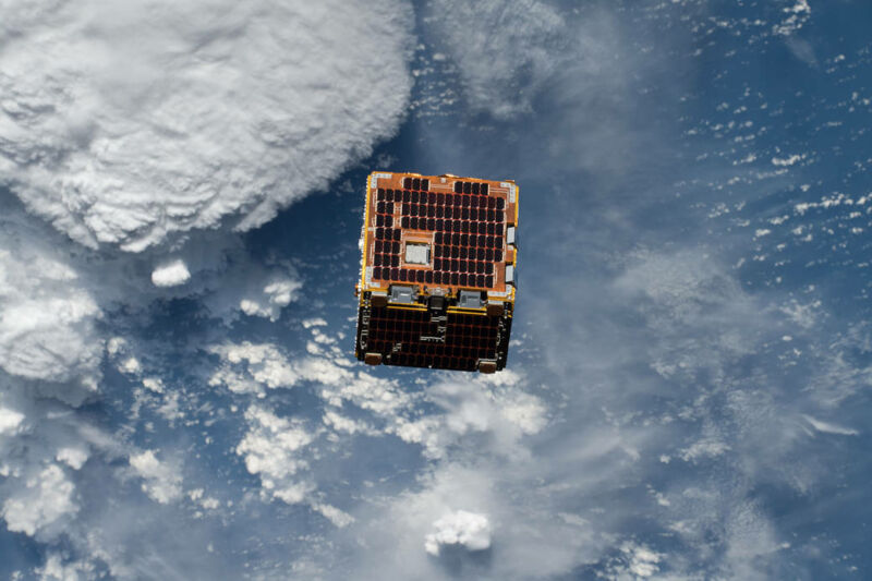 A cube covered in solar panels orbiting above clouds.