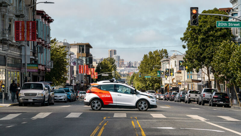 A hatchback with Cruise branding drives through San Francisco.