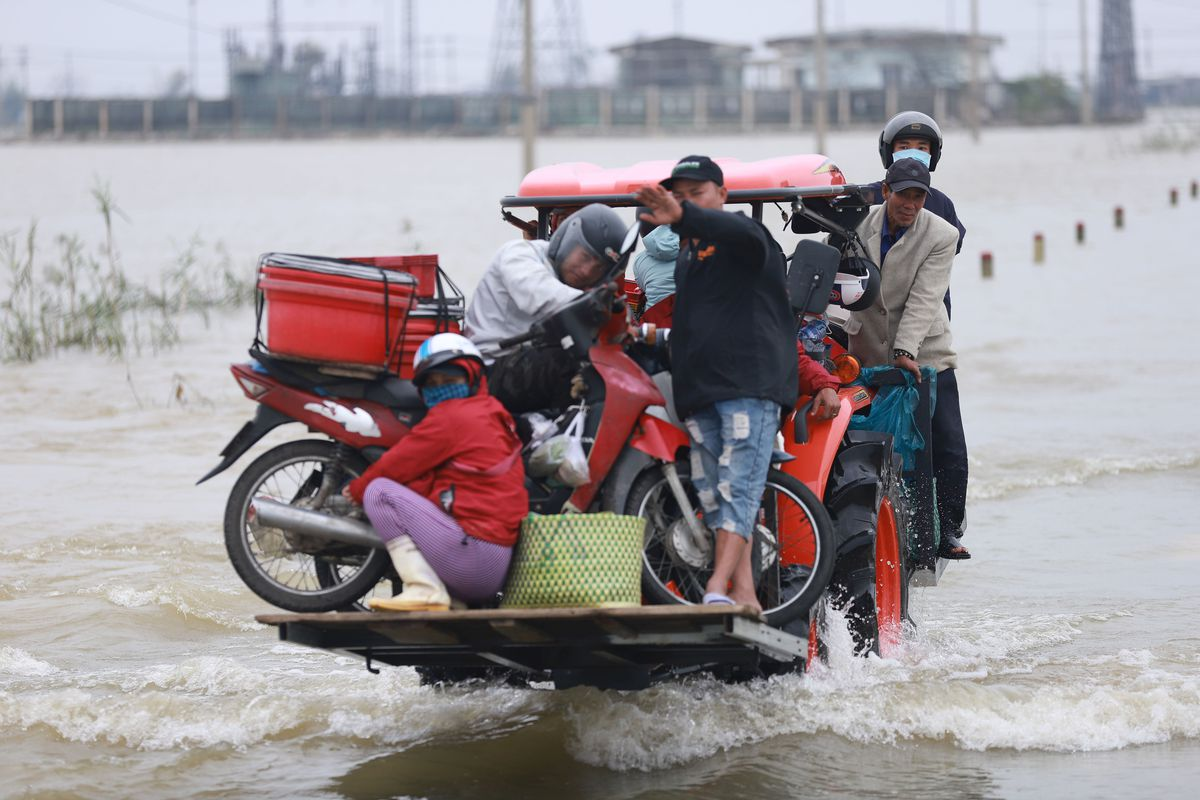 Residents are carried on a forklift truck to dry land through flood waters brought by heavy rain from Typhoon Vamco after it made landfall in Thua Thien Hue province on November 15, 2020.