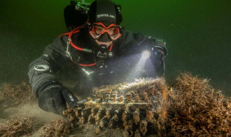 A deep-sea diver examines a heavily encrusted piece of machinery on the seabed.