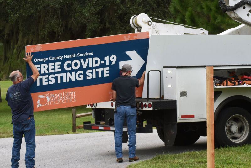Workers removing a sign from a drive-through COVID-19 testing site in Orlando, Fla. in October, 2020.