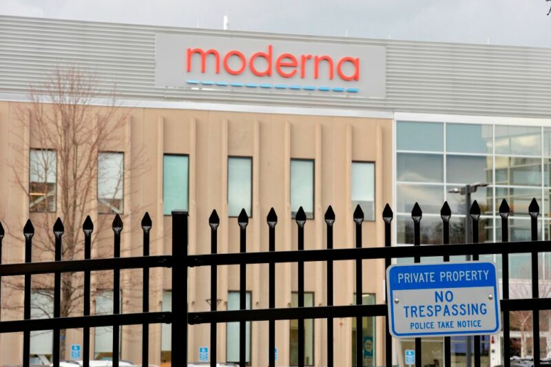 Image of a building with the Moderna logo behind a security fence.