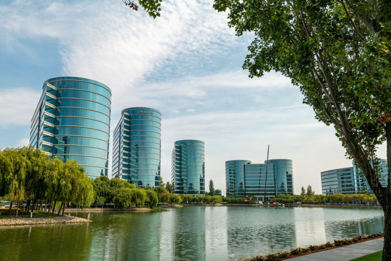 Multistory glass buildings ring a retention pond.