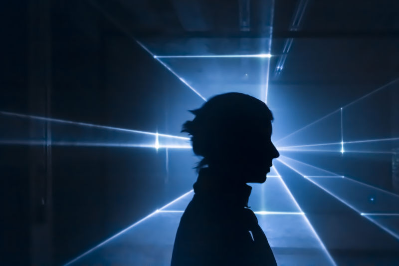 Silhouette of person in front of laser-light projection.