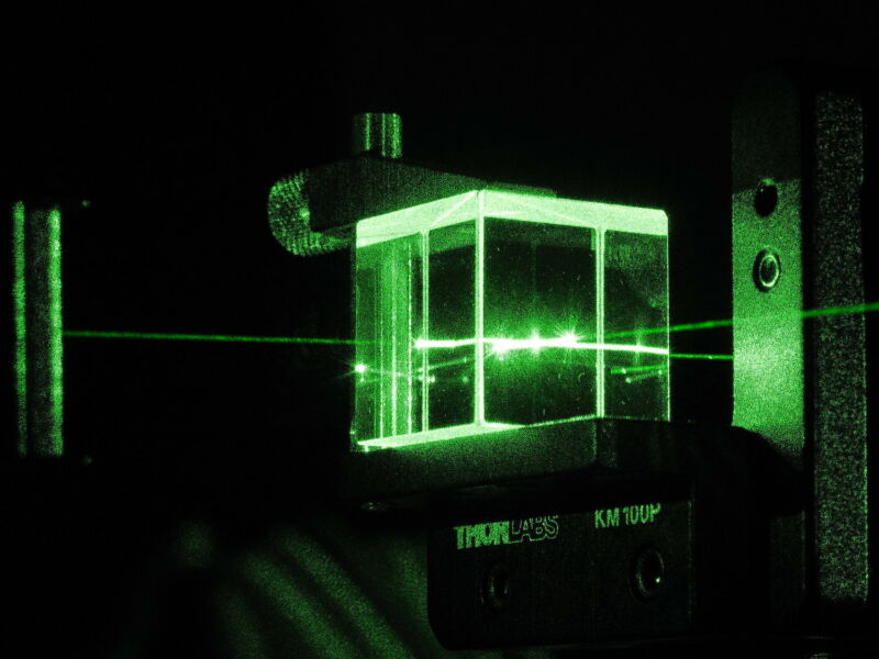 Green lights illuminate what appears to be a glass box.
