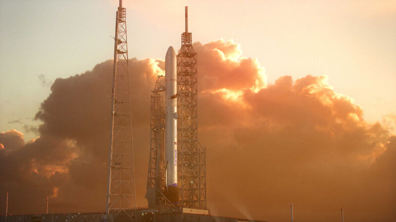 A rocket sits on a launch pad in front of a fiery sunrise.