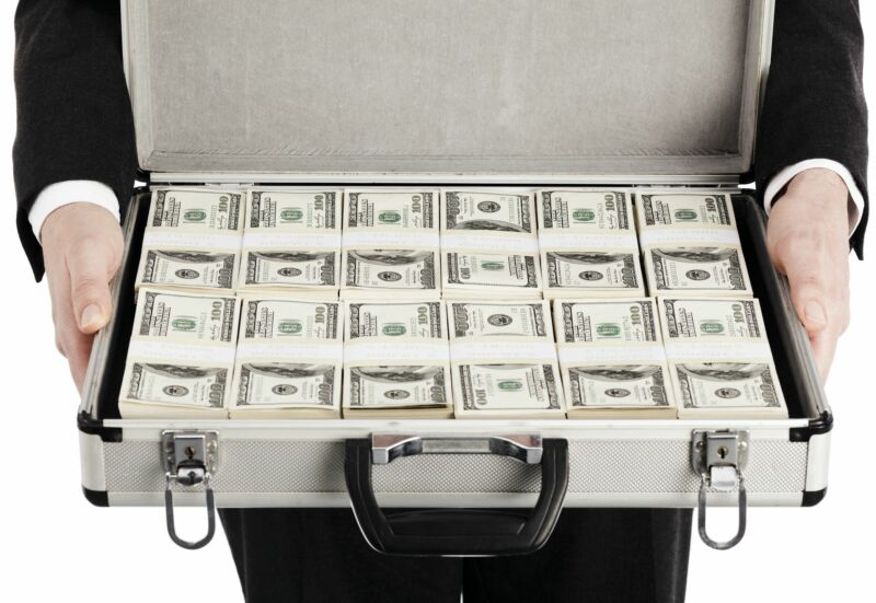 A man holding a briefcase full of money.