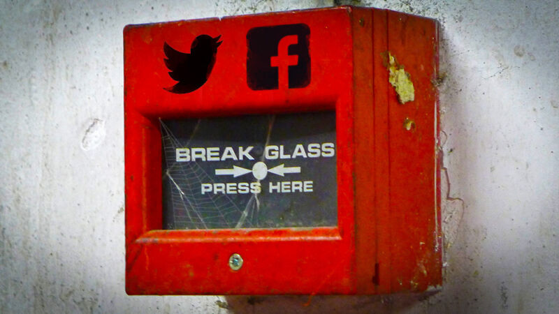 Logos for Twitter and Facebook have been photoshopped onto a hand-operated fire alarm.