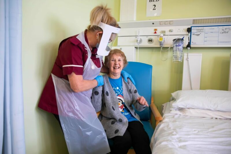 Margaret Keenan, 90, who was the first patient in the United Kingdom to receive the first of two doses of the Pfizer-BioNtech Covid-19 vaccine, reacts as she talks with Healthcare assistant Lorraine Hill, while preparing to leave University Hospital Coventry, in Coventry on December 9, 2020, a day after receiving the vaccine.