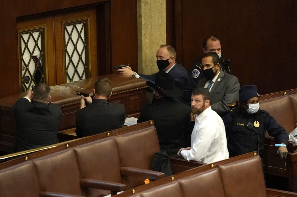 U.S. Capitol police officers draw their guns as an intruder attempts to break through a barricaded door to the House Chamber.