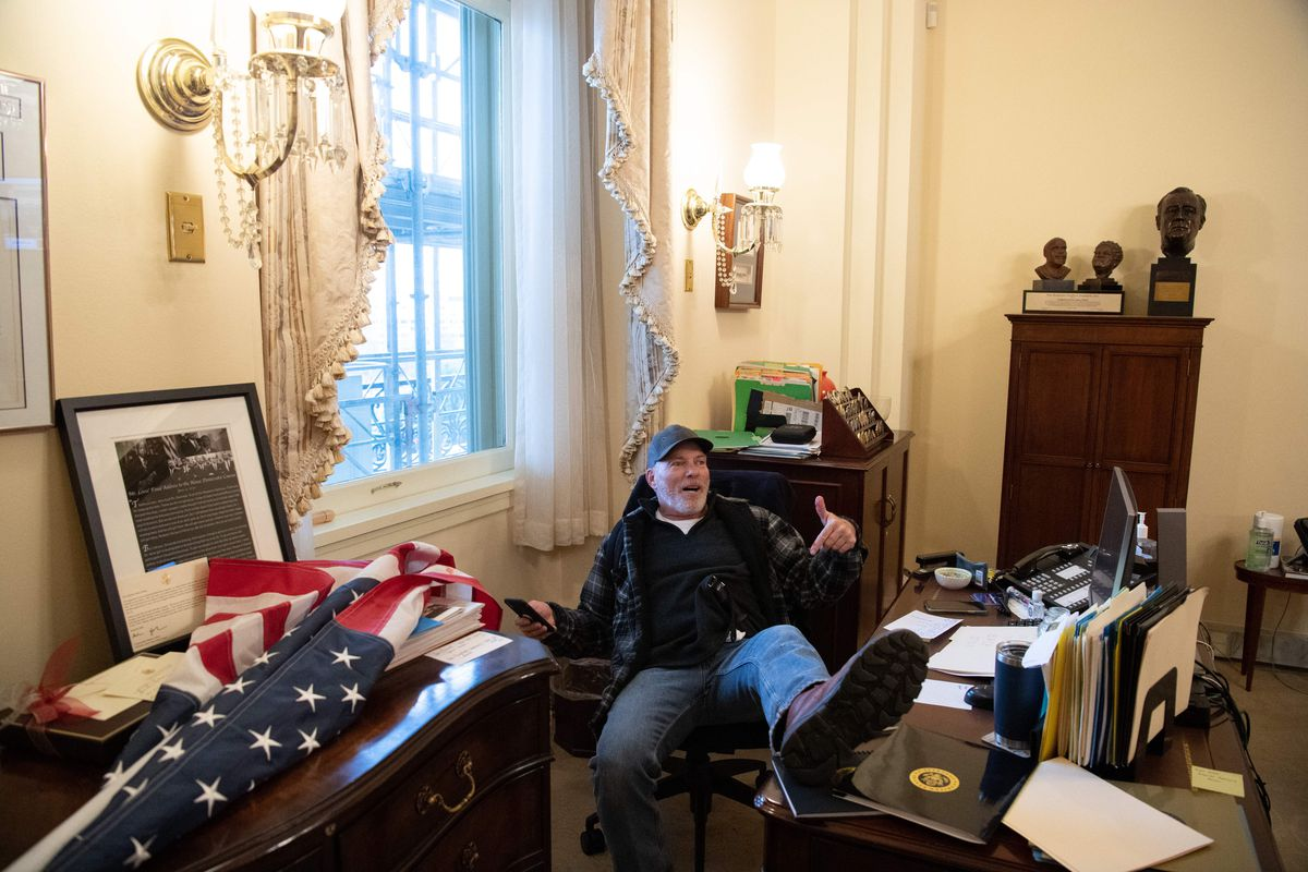 Richard Barnett, a supporter of US President Donald Trump sits inside the office of US Speaker of the House Nancy Pelosi as he protest inside the US Capitol in Washington, DC, January 6, 2021.