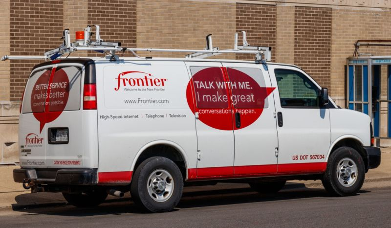 A Frontier Communications service van parked in front of a building.