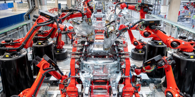 Robot arms work on an assembly line.