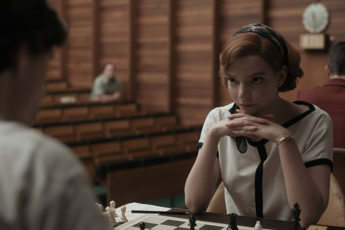 A redheaded woman (Beth) sits in front of a chess board, propping her chin on her hands and watching her opponent.