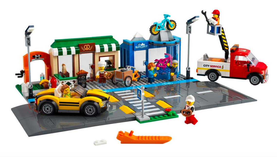 The new official Shopping Street lego set has a tiny blue bike lane next to a large road and small shops.