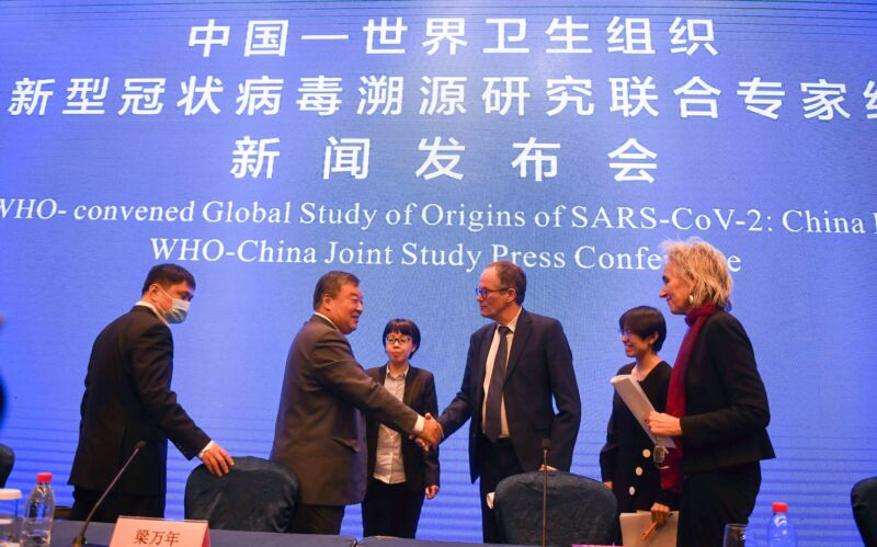 Liang Wannian (2nd L) and Peter Ben Embarek (3rd R) both members of the WHO-China joint study team, shake hands after the WHO-China joint study press conference in Wuhan, central China's Hubei Province, Feb. 9, 2021.