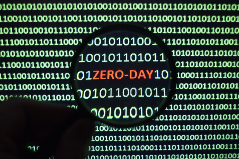 The phrase Zero Day can be spotted on a monochrome computer screen clogged with ones and zeros.