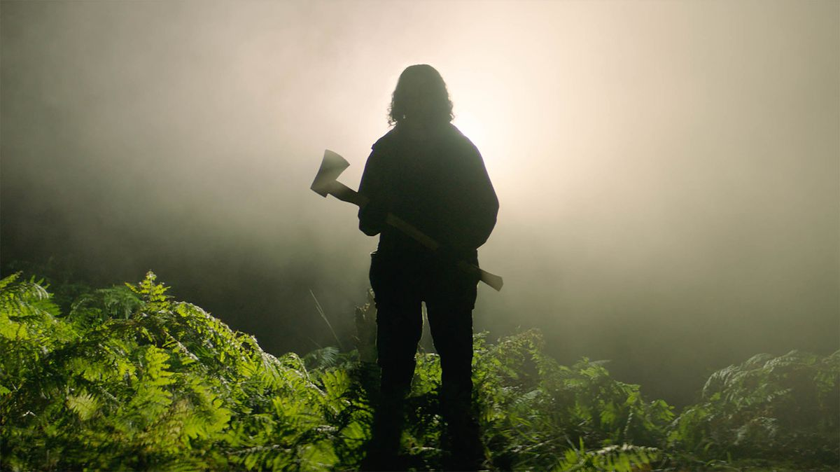 A man silhouetted against a bright, foggy light, holding an axe.