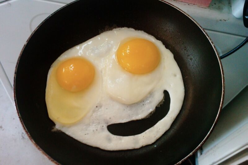 Eggs frying in a pan have been arranged to look like a smiling face.