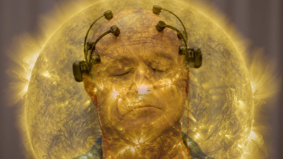 A man's face appears with probes on a headset attached, superimposed against the backdrop of a fiery sun.
